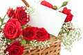 Red roses and blank card in wicker basket Royalty Free Stock Photo