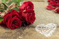 Red roses bouquet with ribbon on stone table Royalty Free Stock Photo
