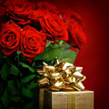 Red roses and golden gift box. Festive decoration Royalty Free Stock Photo