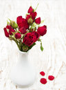 Red roses in vase with on a wooden background Royalty Free Stock Photography
