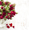 Red roses in vase with on a wooden background Stock Images
