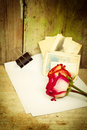 Red roses white paper and old photos on a vintage wooden background Stock Photo