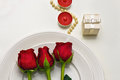 Red Roses on a white plate, candles and giftbox. Romantic composition for Valentine`s Day, Anniversary, Events. Place Royalty Free Stock Photo