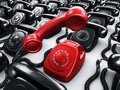 Red rotary phone surrounded by black phones Royalty Free Stock Photo