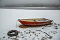 Red rowing boat anchored with tire in snow Royalty Free Stock Photo
