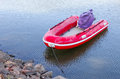 Red rubber boat at the waterside inflatable was tightened Stock Photography