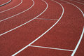 Red running track and white lanes on sport stadium. Royalty Free Stock Photo