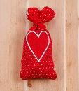 Red sachet bag with a heart on wooden background Stock Photo