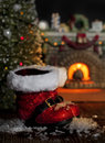 Red santa boots melting snow christmas that have tracked in that is now from warmth of fireplace christmas tree and fireplace Stock Images