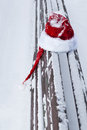 Red santa claus hat on snow covered bench outdoors Stock Photo