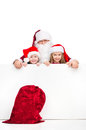 Red santa sac on foreground isolated over white background old claus and two little kids standing behind blank poster Stock Image