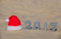 Red Santa's hat lies on the beach, next to the sand are the numbers of the new year with silver sequins. Royalty Free Stock Photo