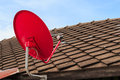 Red satellite tv receiver dish on the old tiles roof closeup Stock Photo