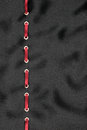 Red satin ribbon inserted in the gold rings on black silk Royalty Free Stock Photo