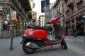 Red scooter parked in one of the Milan central streets Royalty Free Stock Photo