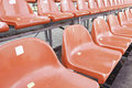 Red seats in a grandstand detail of football field spectators and sport Royalty Free Stock Photo