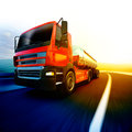 Red semi truck on blurry asphalt road under evening sky and suns Royalty Free Stock Photo