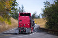 Red Semi trucks back convoy on winding fall road Royalty Free Stock Photo