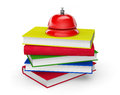 Red service bell standing on stack of books a white background Stock Photos