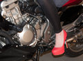 Red shoe girl on a motorbike with shoes on Stock Images