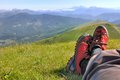 Red shoes walking an lying hiker front of a mountainous landscape Stock Image