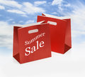 Red shopping bags two summer sale against sky background Stock Photos
