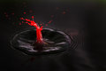 Red shot beautiful image of a drop of cream falling into dark water in the shape of a little man getting Royalty Free Stock Photos