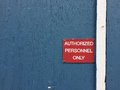 Red sign on blue wooden wall reading authorized personnel only a painted with a white stripe a reads security keep out restricted Royalty Free Stock Photography