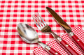Red silverware on a red checkered napkin and table cloth Royalty Free Stock Photos