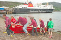 Red skiff hauled out of the sea a partan at ullapool on th july at end world championship competition Royalty Free Stock Photo