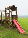 Red slide from wooden crawl construction on modern kids playground Royalty Free Stock Photo