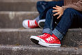 Red sneakers on a kids feet, sitting on stairs