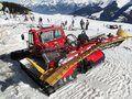 Red snowcat waits to groom the snow Royalty Free Stock Photo