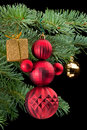 Red snowman holding golden gift box on pine branch Stock Images