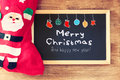 Red sock and blackboard with merry christams greeting and colorful icons. christmas card concept