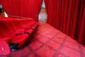 Red soft seats in picture show hall with curtains and wooden door Stock Photography