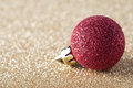 Red Sparkly Bauble on Gold Glitter Royalty Free Stock Photography