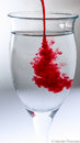 Red splash in glass of water. Royalty Free Stock Photo
