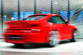 Red sports car on rotating platform turns a long exposure Royalty Free Stock Photo