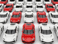 Red sports cars in formation amongst white cars