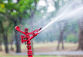 Red sprinkler the spraying water in garden Stock Photos