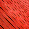 Red stained timber slats as abstract pattern background viewed diagonally to create Stock Photography