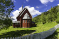 Red stave church on a sunny day in small town of norway with green yard and fence as horizontal shot Stock Photo