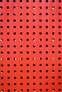 Red steel plate background wall with lot of holes Royalty Free Stock Photos