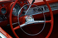Red steering wheel and dashboard with chrome on dash and gearshift Stock Photos