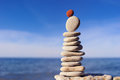 Red stone on the top balance of of stack of white pebbles Royalty Free Stock Photos