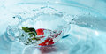 Red strawberries fall into blue water and create a splash Royalty Free Stock Photo
