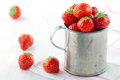 Red strawberries in an old metal measurement cup Royalty Free Stock Photo