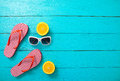 Red striped flip flops, red sunglasses and orange fruit on blue wooden background. Top view and summer time. Royalty Free Stock Photo
