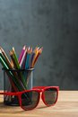 Red sun glasses with bunch of color pencils in a stand on brown wooden table Stock Photography